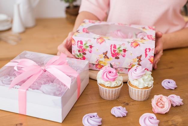 Close-up de cupcakes lindos em uma caixa de presente. cupcakes caseiros com creme e merengue em embalagens festivas