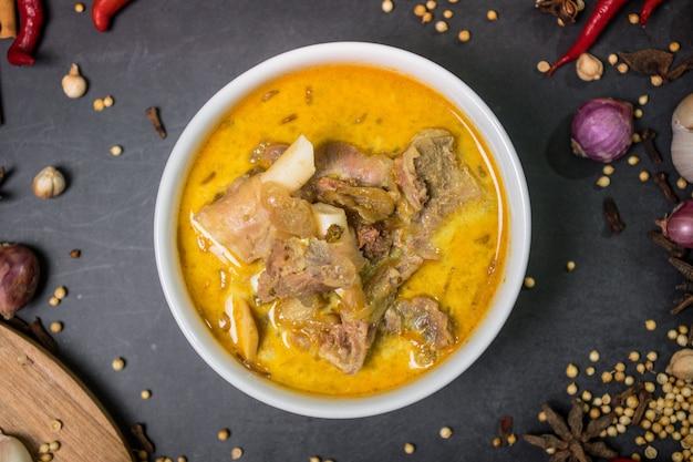 Close up de curry de carneiro indonésio com molhos vermelhos na tigela e temperos um dos menus aqiqah