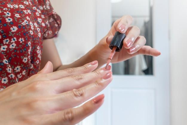 Close up de dedos de mulher está fazendo unha polonês