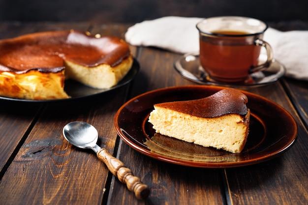 Close up de delicioso cheesecake basco queimado em mesa rústica