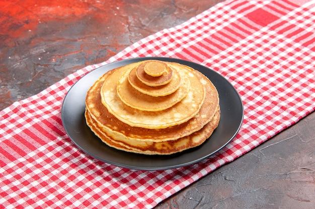 Close-up de deliciosos panacakes em uma toalha vermelha despojada