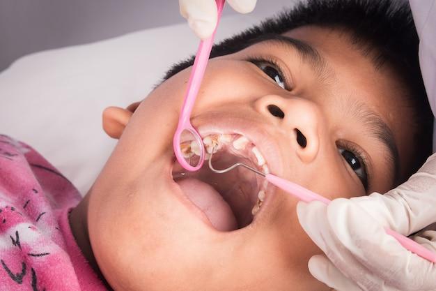 Close up de dentes menino com examinado por um dentista