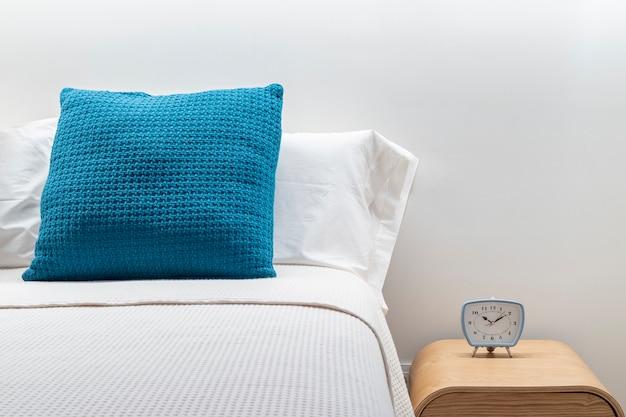 Close-up de despertador em uma mesa de cabeceira ao lado de uma cama de dormir