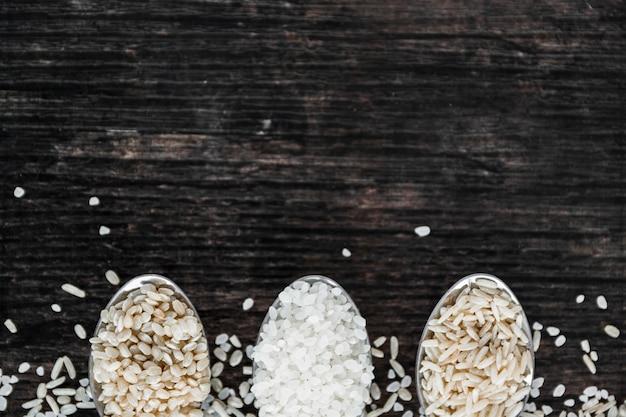 Close-up, de, diferente, tipo, de, arroz, em, colher, ligado, madeira, fundo