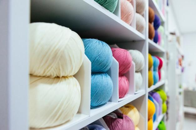 Close-up de diferentes fios de lã, organizados por cores em uma prateleira