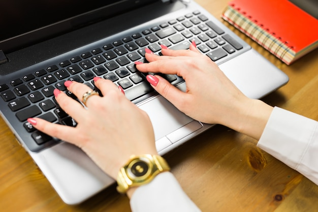 Close-up de digitar as mãos femininas no teclado