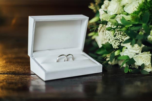 Close-up de dois anéis de casamento de luxo em uma elegante caixa branca em cima da mesa. acessórios do casamento