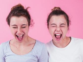Close-up, de, dois, femininas, amigos, shouting, contra, fundo cor-de-rosa
