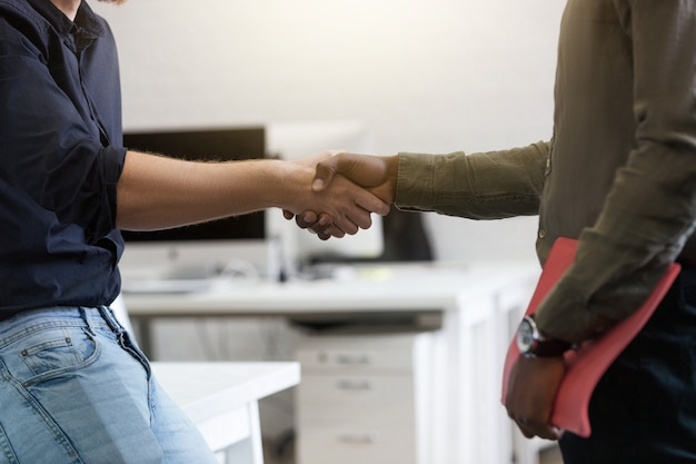 Close-up de dois jovens colegas, apertando as mãos