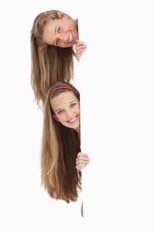 Close-up, de, dois, longo, cabelo, estudantes, atrás de, um, em branco, sinal
