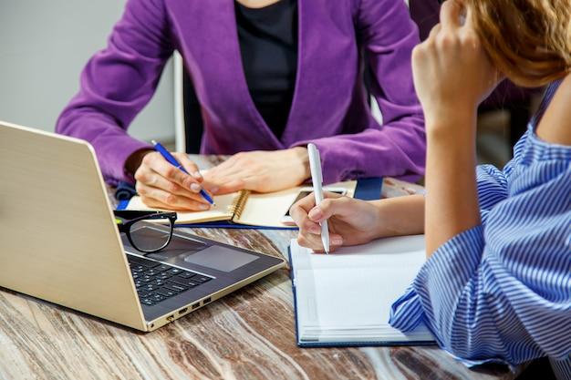 Close up de dois pares de mãos das mulheres em um escritório