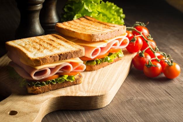 Close-up de dois sanduíches com bacon, salame, presunto e legumes frescos na tábua de madeira rústica. conceito de sanduíche de clube.