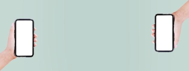 Close-up de dois smartphones em mãos na superfície panorâmica de cor verde pastel com espaço de cópia no meio.