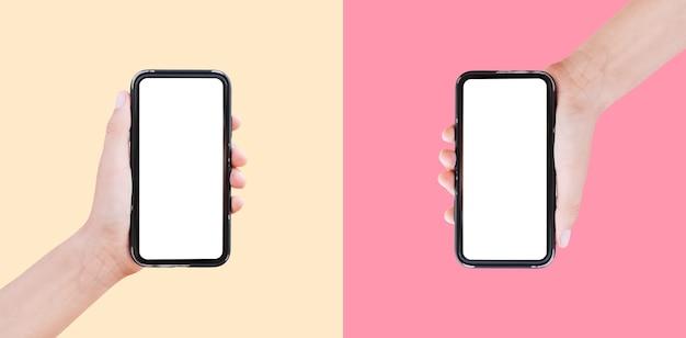 Close-up de dois smartphones nas mãos em superfícies de cores pastel de amarelo e rosa.