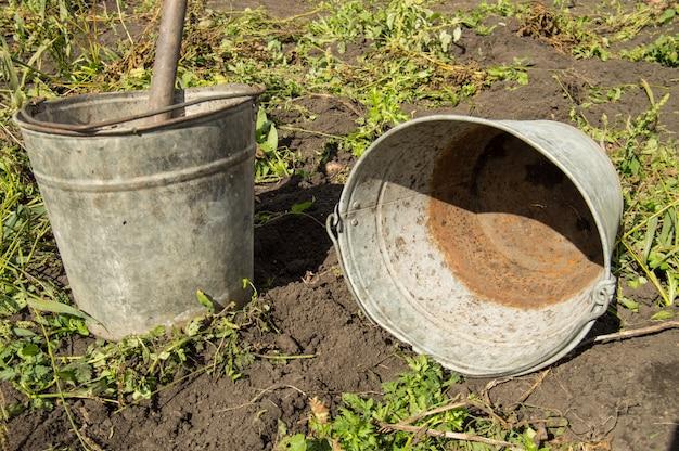 Close-up de dois velhos baldes de ferro enferrujado sujo no fundo do solo e grama no jardim