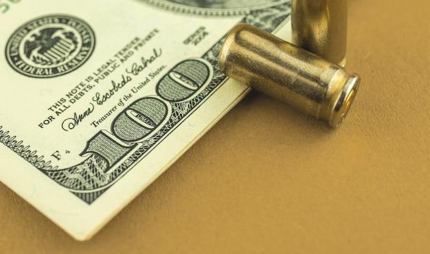 Close-up de dólar e bala, dinheiro do crime e fundo do conceito de máfia