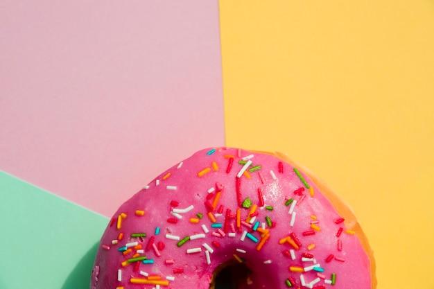 Close-up de donut com polvilha contra amarelo; rosa; e pano de fundo verde menta