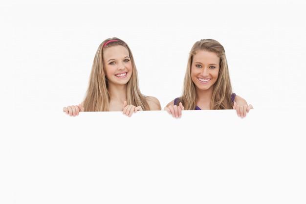 Close-up de duas jovens mulheres segurando um sinal em branco