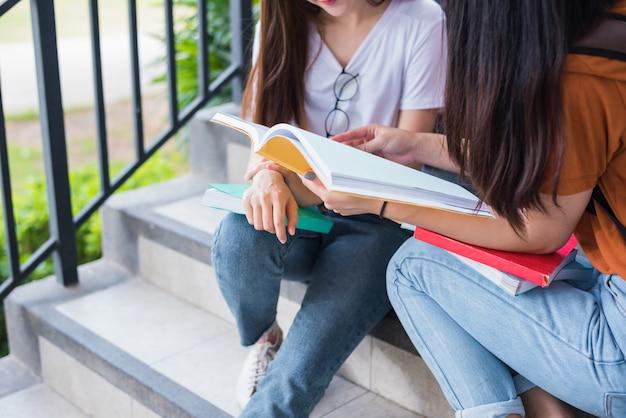 Close up de duas meninas de beleza asiáticas lendo e livros de tutoria