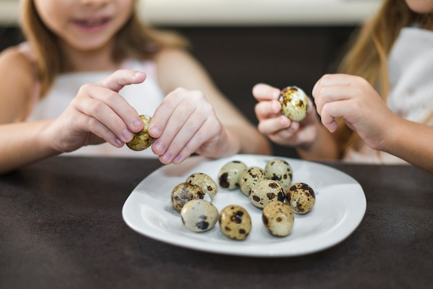 Close-up, de, duas meninas, descascando, codornizam ovos, em, prato, casa