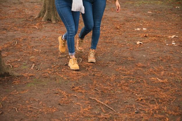 Close up de duas mulheres em botas andando no parque