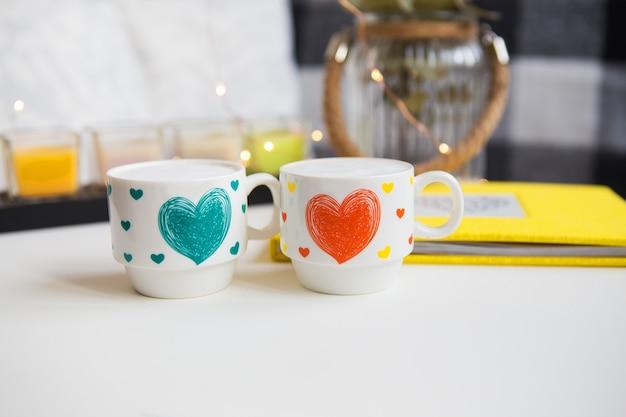 Close-up de duas xícaras de cappuccino em um fundo de velas e um vaso com eucalipto