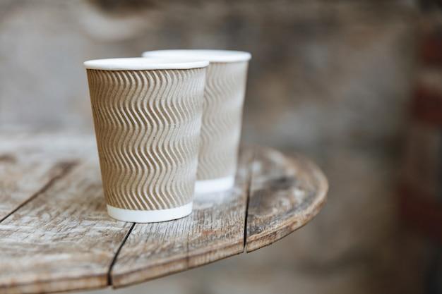 Close-up de duas xícaras marrons descartáveis de café com sabor quente