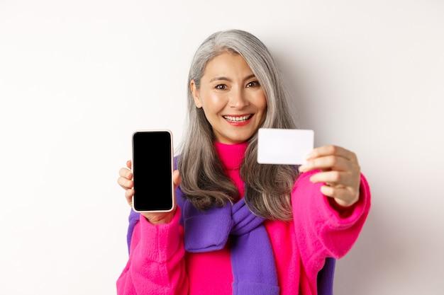 Close-up de elegante mulher coreana sênior mostrando a tela do celular vazia e cartão de crédito de plástico, sorrindo feliz, de pé em branco.