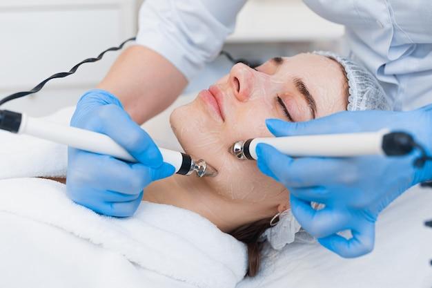 Close-up de eletrodos do aparelho de terapia de microcorrente no rosto de uma linda jovem.