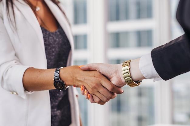 Close-up de empresárias apertando as mãos, cumprimentando-se antes do encontro.