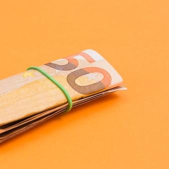 Close-up, de, enrolado, nota euro, amarrada, com, borracha, ligado, um, laranja, fundo