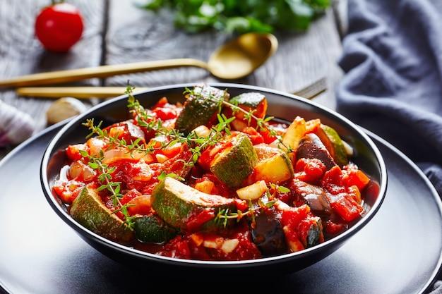 Close-up de ensopado de legumes, berinjela, cebola, abobrinha com molho de tomate, alho e ervas em uma tigela preta sobre uma mesa de madeira, vista panorâmica de cima