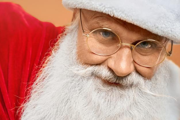 Close-up de envelhecido papai noel com barba grisalha em óculos