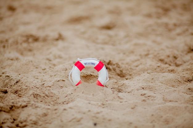 Close-up de escavação em miniatura lifebuoy na areia na praia