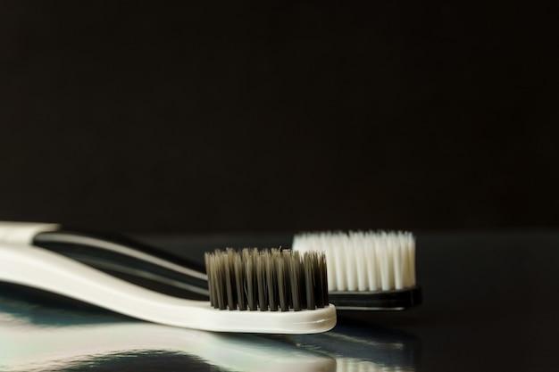 Close-up de escovas de dente preto e brancas em um fundo preto. conceito de higiene oral