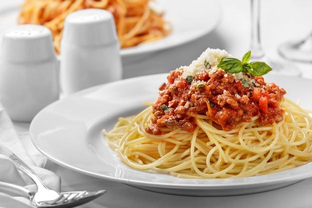 Close up de espaguete italiano à bolonhesa coberto com queijo e manjericão em um prato branco simples