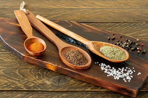 Close up de especiarias brilhantes pimenta, páprica, açafrão, pimenta em colheres de madeira.