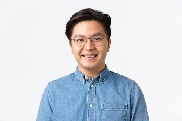 Close-up de esperançoso cara asiático fofo com aparelho, sorrindo para a câmera, satisfeito com atendimento odontológico profissional na clínica de estomatologia, parecendo satisfeito, em pé sobre um fundo branco