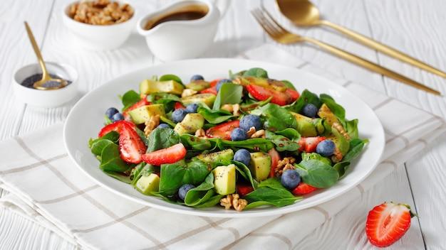 Close-up de espinafre, abacate, nozes, morango e salada de mirtilo com vinagre balsâmico e sementes de papoula