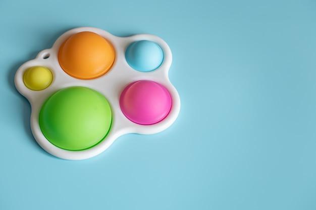 Close-up de exibição simples anti-stress de brinquedo moderno em um espaço de cópia de fundo azul.