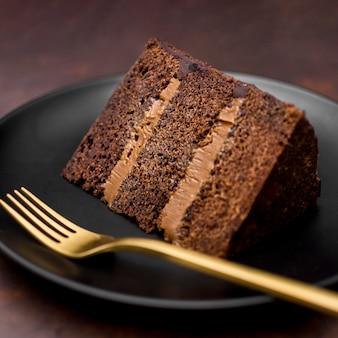 Close-up de fatia de bolo no prato com garfo de ouro
