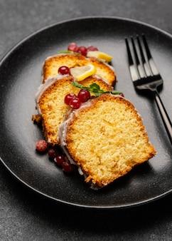 Close-up de fatias de bolo no prato com garfo e frutas