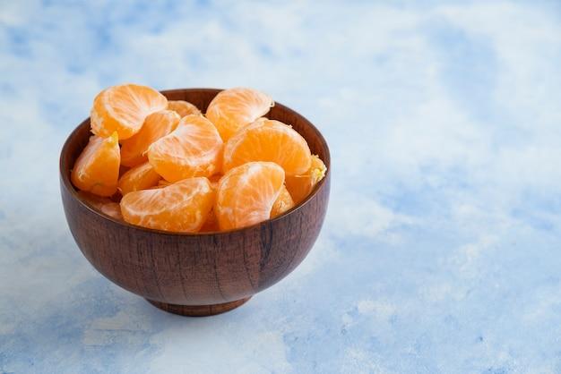 Close up de fatias de mandarim em uma tigela de madeira na superfície azul
