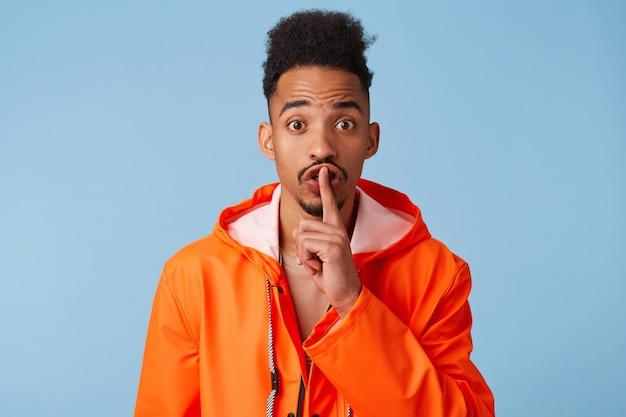 Close up de feliz jovem afro-americano de pele escura com capa de chuva laranja, conta informações secretas, demonstra gesto de silêncio, pede para ficar quieto isolado.