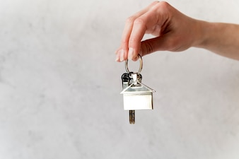 Close-up, de, femininas, passe segurar, prata, casa, keychain, contra, parede concreta