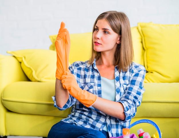 Close-up, de, femininas, porteiro, sentando, frente, sofá amarelo, desgastar, um, laranja, luvas