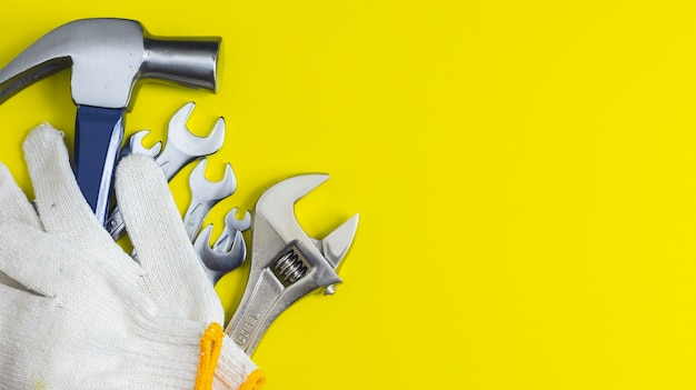Close-up de ferramentas de artesão em um fundo amarelo, martelo, chave inglesa, luvas mecânicas, vista superior
