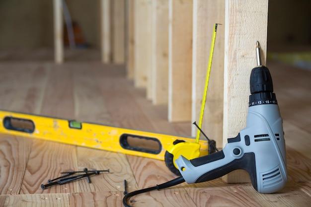 Close-up de ferramentas profissionais: chave de fenda elétrica, nível e fita métrica no fundo da moldura de madeira para futura parede no quarto do sótão em reconstrução
