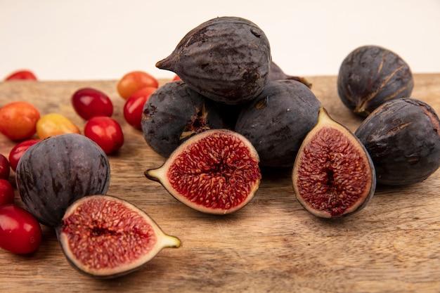 Close-up de figos pretos doces em uma placa de cozinha de madeira com cerejas da cornalina isoladas em uma parede branca