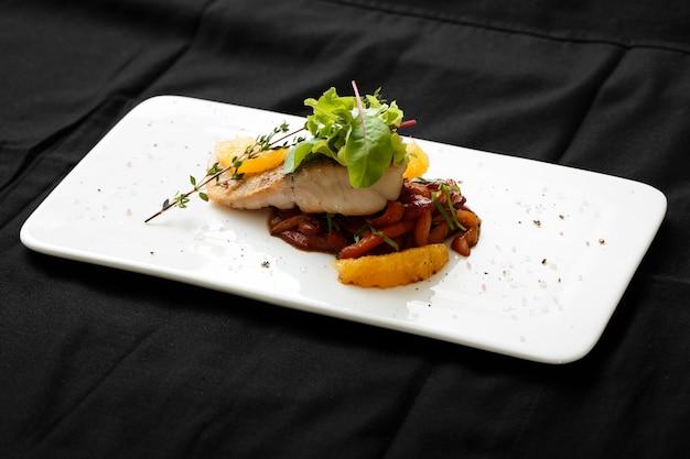 Close-up de filé de peixe branco com ensopado de legumes